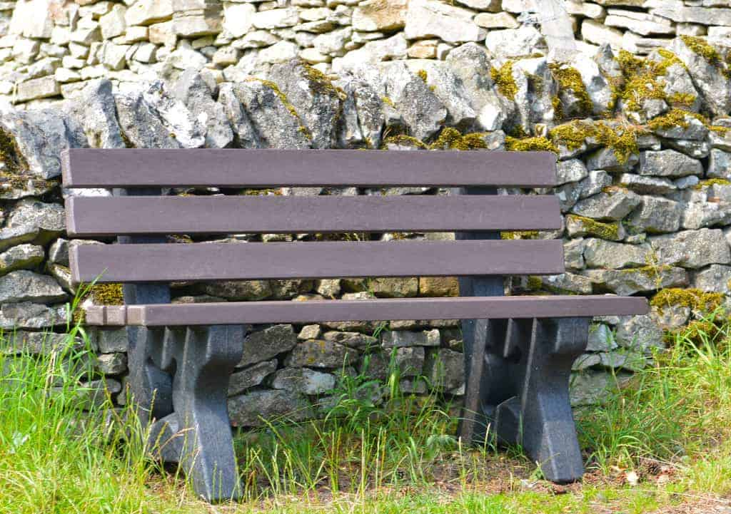 Recycled plastic Peak bench in front of dry stone wall